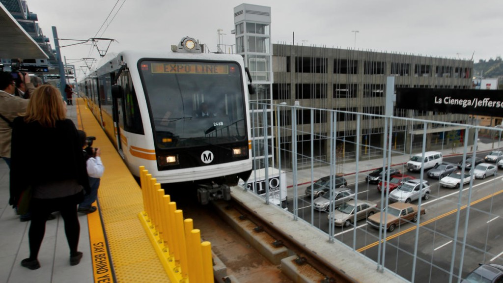 A Metro Expo light rail cars pulls into La Cienega/Jefferson station while traffic down below plods along during morning rush hour. (Los Angeles Times)