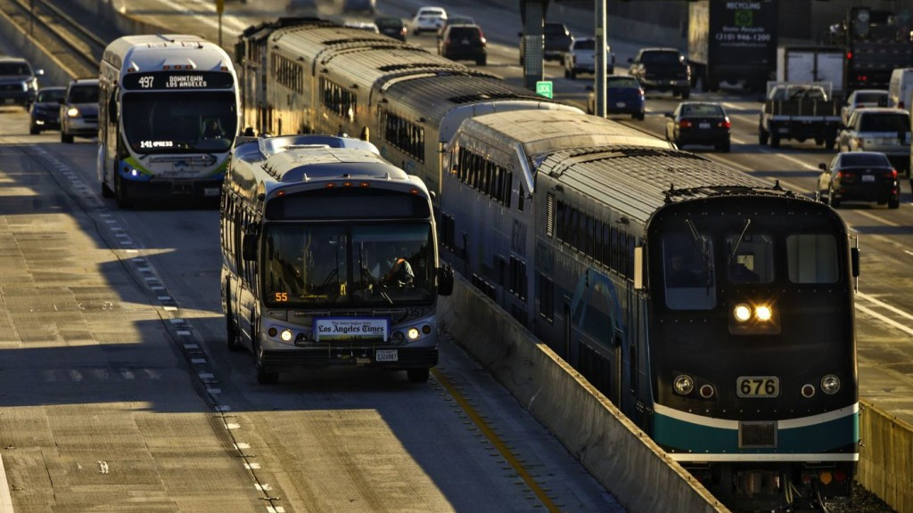 A Metrolink train travels along I-10 toward Union Station. State grants announced Thursday aim to improve rail and bus services. (Irfan Khan / Los Angeles Times)